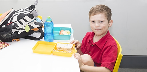 Boy with healthy lunchbox and schoolbag