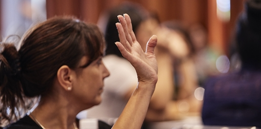 Woman with her hand up at a seminar