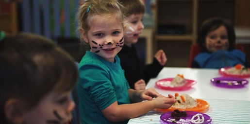 child eating food at party with her face painted like a cat