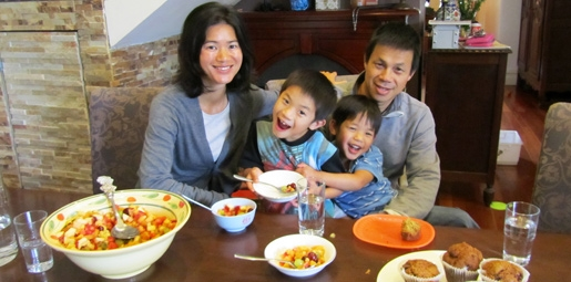 Asian parents with their two young sons enjoying bowls of fruit and water