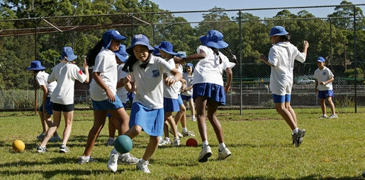 Primary school children playing ball games outdoors
