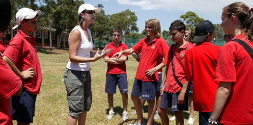 teacher coaching teenage kids on school sports ground