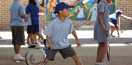 school child playing tennis