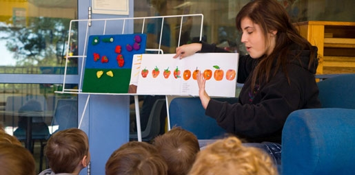 teacher reading hungry caterpillar book to kids