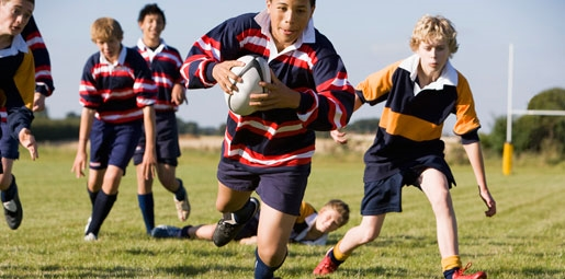 Early teenage boys playing rugby