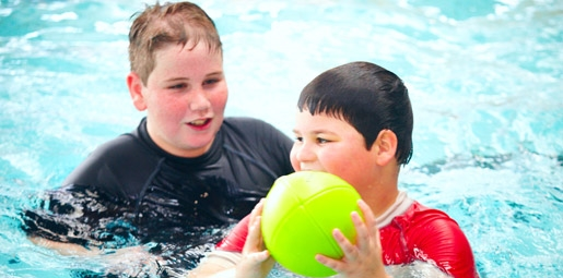 two boys in pool with yellow ball
