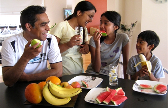 Family eating bananas, apples and watermelon